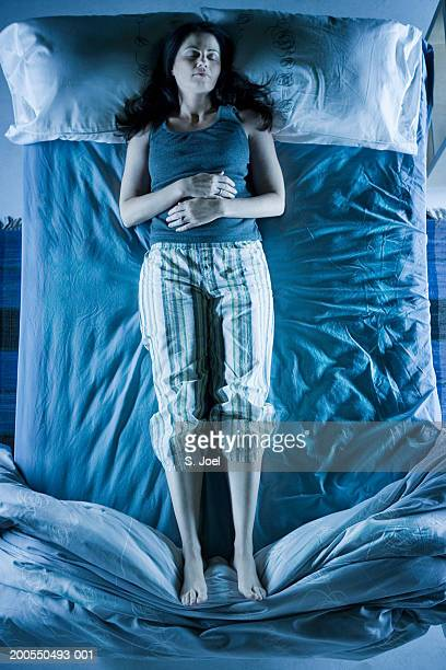 Woman sleeping in middle of bed