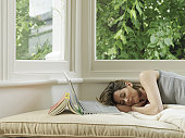 Woman sleeping in window alcove by book and laptop