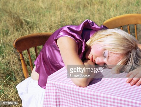 Woman sleeping on a table : Stock Photo
