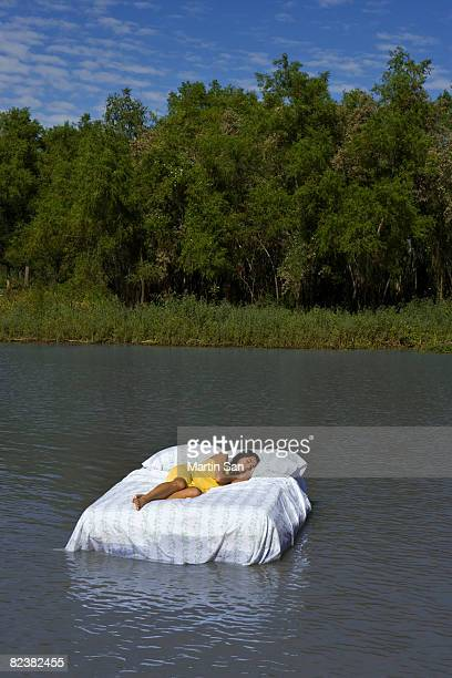 Woman sleeping on bed floating in water