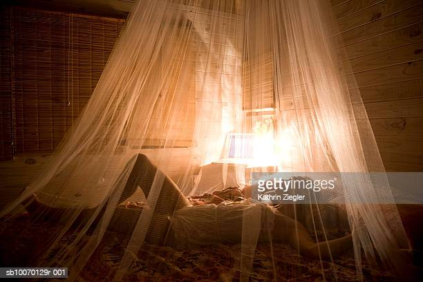 Woman sleeping on bed with mosquito net in beach house