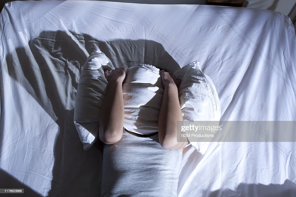 Woman sleeping on bed with pillow on face : Stock Photo