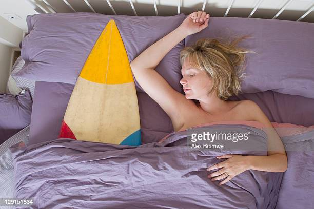 Woman sleeping on bed with surfboard