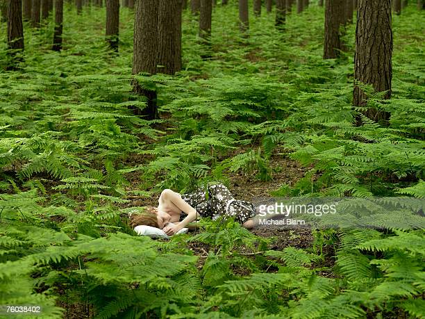 Woman sleeping on pillow in forest