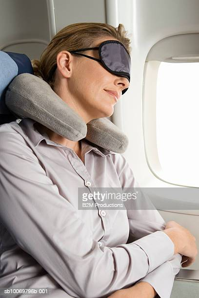 Woman sleeping on plane wearing eye mask