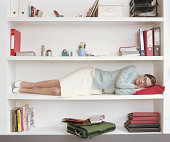 Woman sleeping on shelf of large bookcase