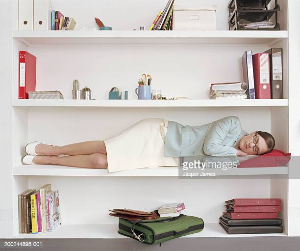 Woman sleeping on shelf of large bookcase