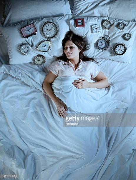 Woman sleeping with lots of alarm clocks