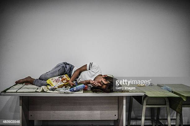 A woman sleeps at the emergency shelter set at a primary school on August 13 2015 in Tianjin China Over 500 injured and evacuated people stay at the...
