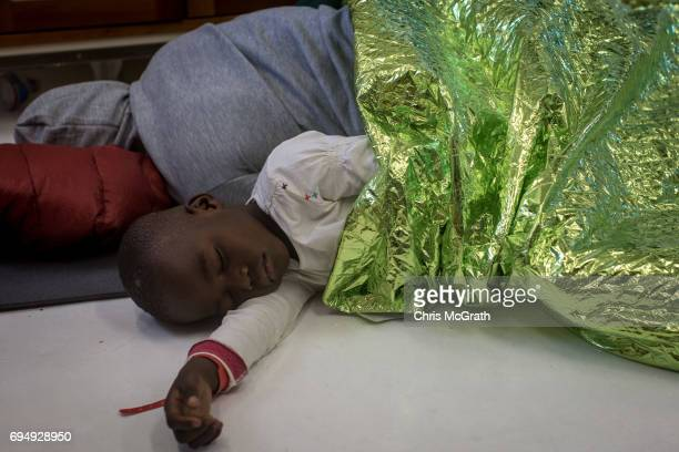 A woman sleeps next to her child on the floor of the medical clinic onboard the Migrant Offshore Aid Station Phoenix vessel enroute to Italy on June...