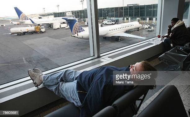 A woman sleeps on a bench at LaGuardia Airport December 21 2007 in the Queens borough of New York City Travelers nationwide are heading home for the...