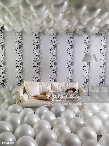 Woman sleeps on sofa with an abundance of balloon