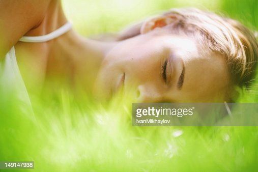 A woman sleeps on the green grass : Stock Photo