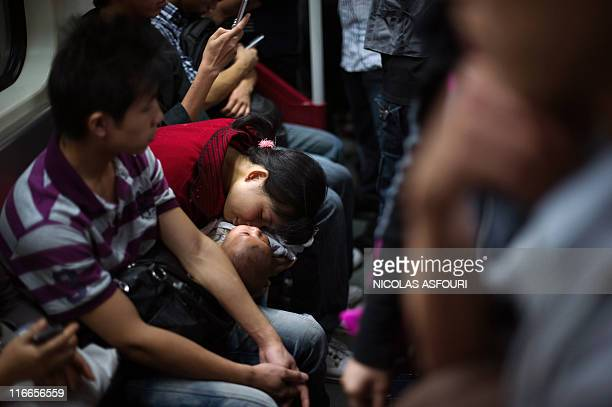 A woman sleeps with her baby on the subway in Guangzhou on November 11 2010 the venue of the 16th Asian Games for which China has poured billions of...