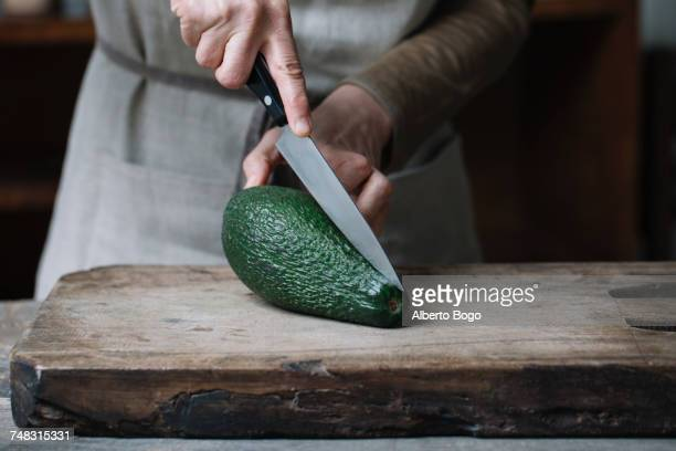 Woman slicing avocado on chopping board, mid section