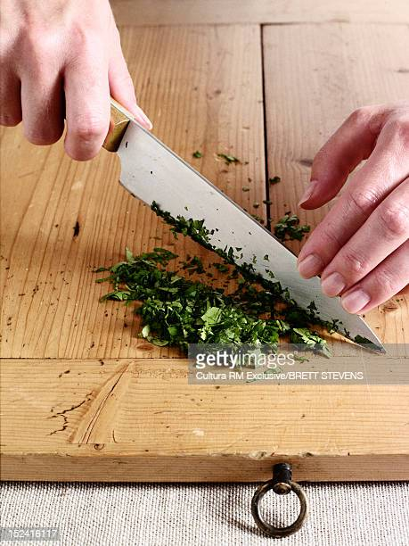 Woman slicing herbs on wooden board