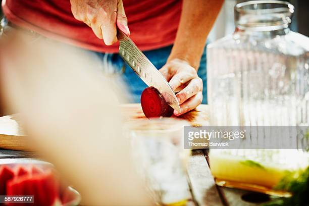 Woman slicing organic beet on cutting board