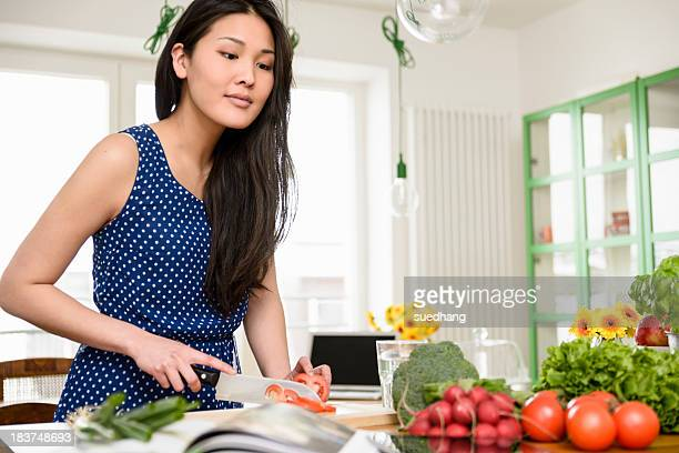Woman slicing tomatoes looking at digital tablet
