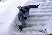 A woman slips and fell on a wintry staircase. Fall on smooth steps