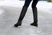 Woman slips on slippery road covered with ice. Concept of injury risk in winter. Close shot.