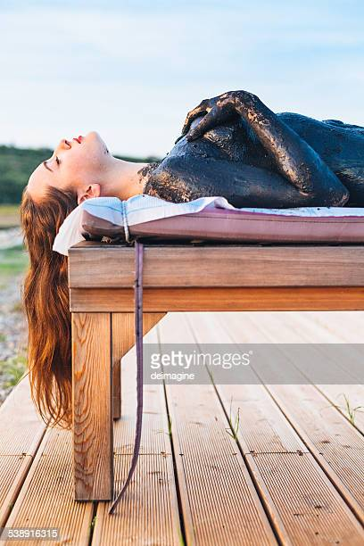 Woman sludge treatment during sunset