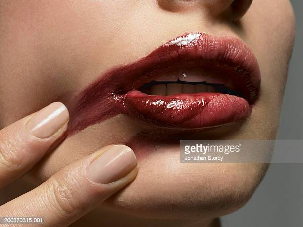 Woman smearing lipstick on face, close-up of mouth