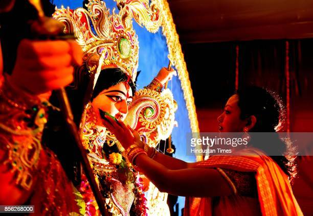 A woman smears sindoor on Durga Idol during Sindoor Khela on the final day of the Durga Puja festival on the occasion of Vijayadashami which is...