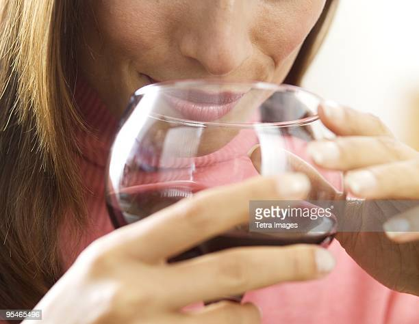 A woman smelling a glass of red wine