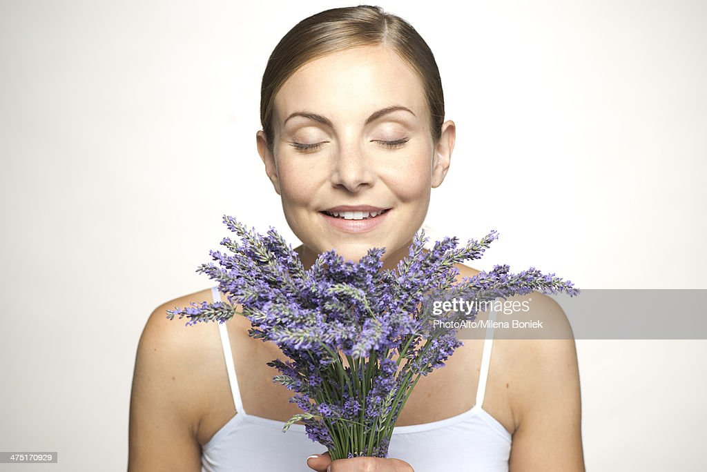 Woman smelling bouquet of fresh lavender with eyes closed