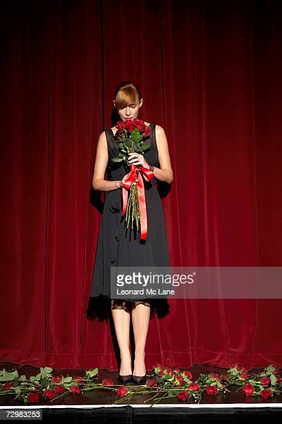 Woman smelling bunch of roses on stage