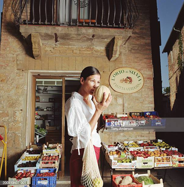 Woman smelling cantaloupe at outdoor fruit stand