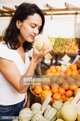 woman smelling cantaloupe melon at market stall side view stock foto getty images. Black Bedroom Furniture Sets. Home Design Ideas