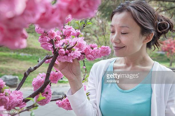 Woman smelling cherry blossoms with eyes closed.