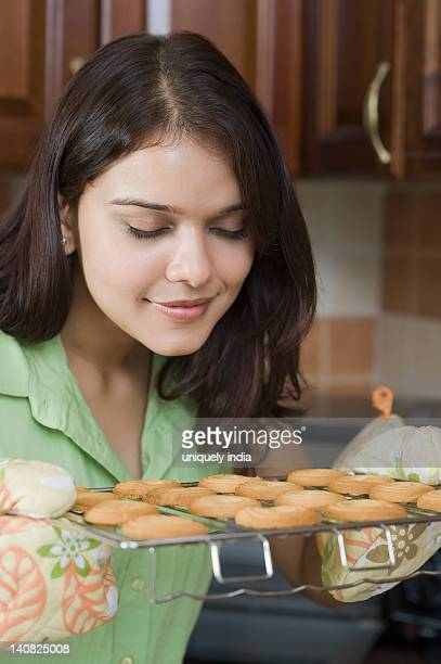 Woman smelling cookies on a cooling rack