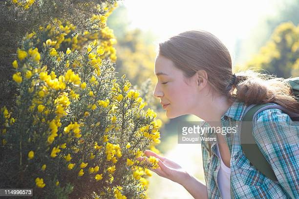 Woman smelling flowers in countryside.