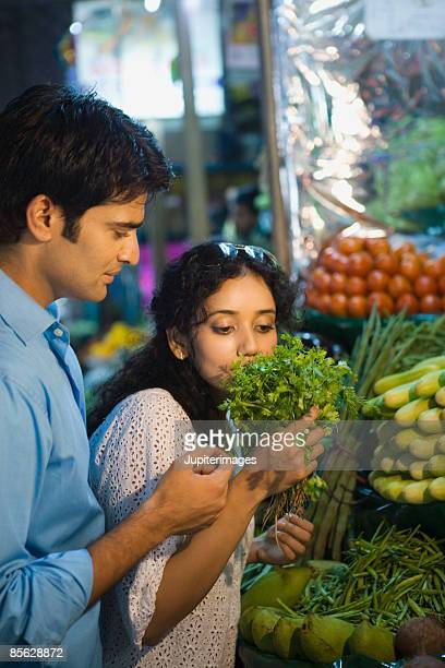 Woman smelling fresh coriander at market
