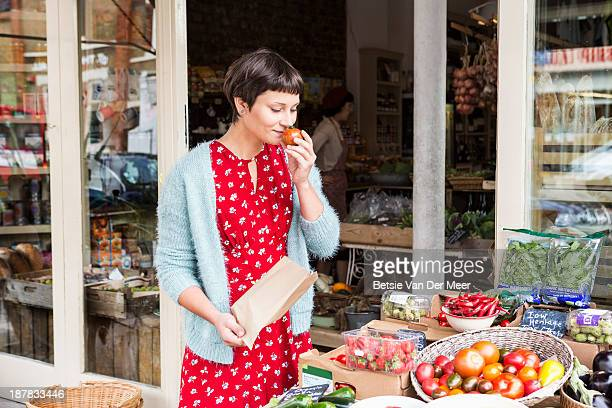 Woman smelling fresh tomato at organic farm shop.