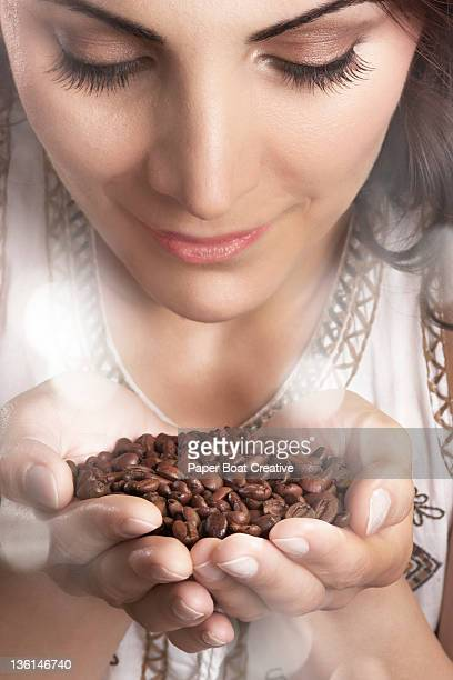 woman smelling freshly roasted coffee beans