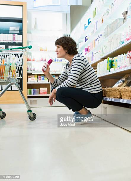 woman smelling on creme in supermarket