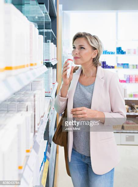 woman smelling on lotion in supermarket