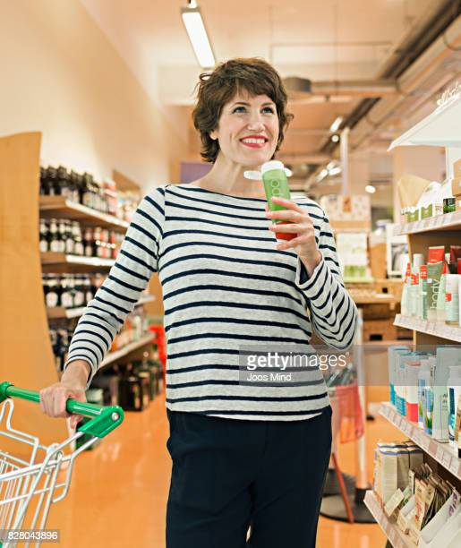 woman smelling on shampoo in supermarket