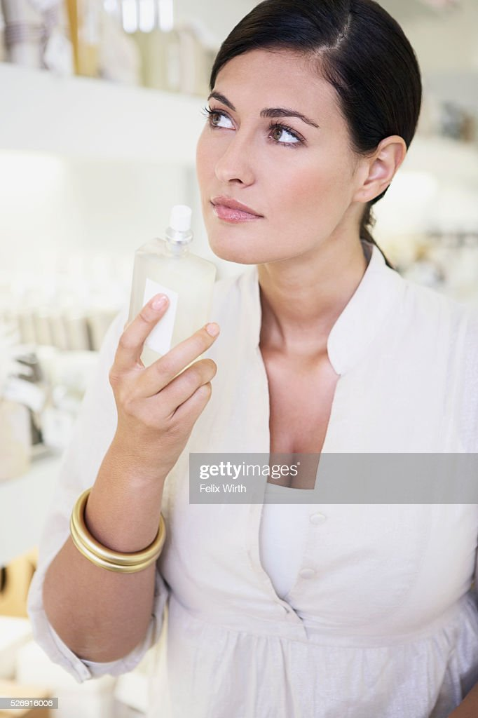 Woman smelling perfume : Foto de stock