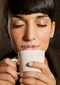 Woman smelling steaming cup of coffee