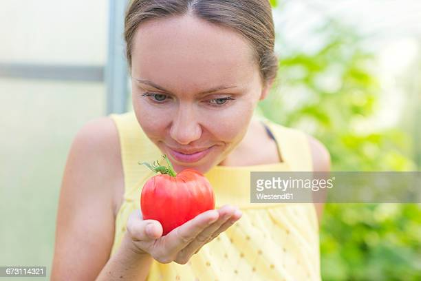 Woman smelling tomato