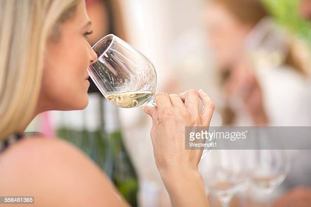Woman smelling white wine on a wine tasting session