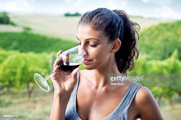 Woman Smelling Wine Near a Vineyard