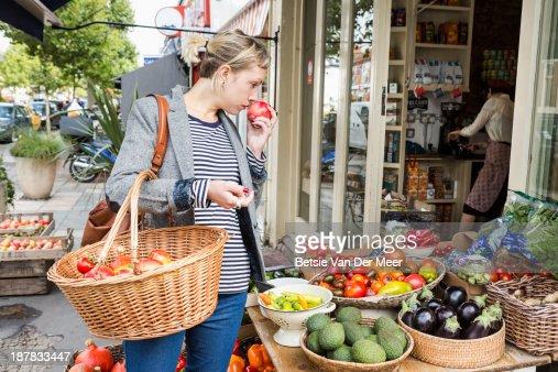Woman smells fruit shopping in fruitstall.