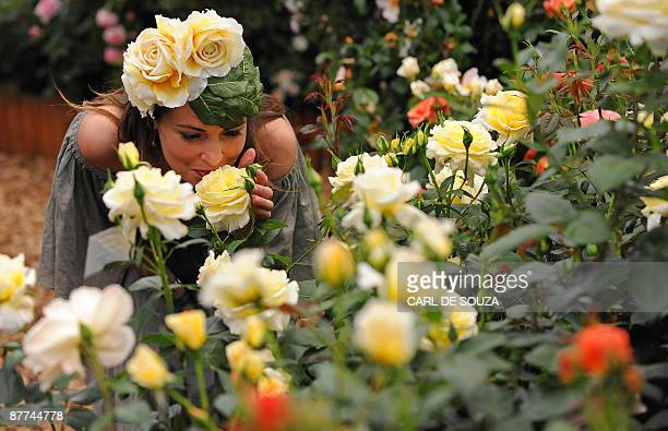 A woman smells roses during the press view of the Chelsea flower show in London on May 18 2009 Originally known as the Great Spring Show the Chelsea...