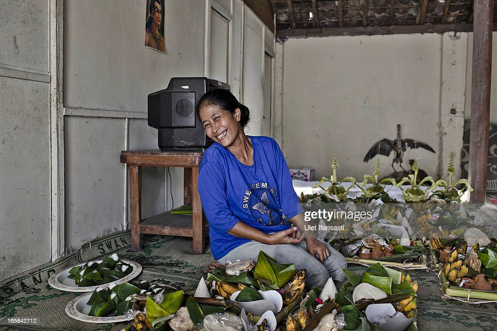 A woman smile as she prepares foods as an offering during the Cembengan ritual 'Manten Tebu' on April 6, 2013 in Yogyakarta, Indonesia. The Cembengan ritual, performed to bring about a good season's sugarcane crop, is held annually before the milling and processing season starts in Indonesian sugar mills.