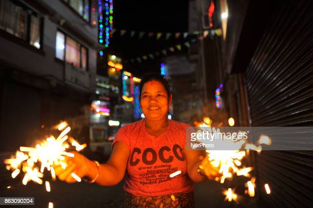 A woman smiles as holding beautiful sparklers in hands during Laxmi Puja as the procession of Tihar or Deepawali and Diwali celebrations at Kathmandu...